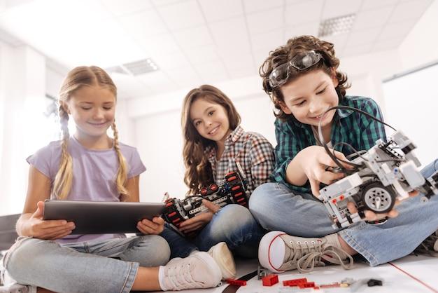 Estudando o conceito de ciência. crianças alegres e curiosas encantadas sentadas na sala de aula de ciências e usando gadgets e dispositivos enquanto expressam alegria