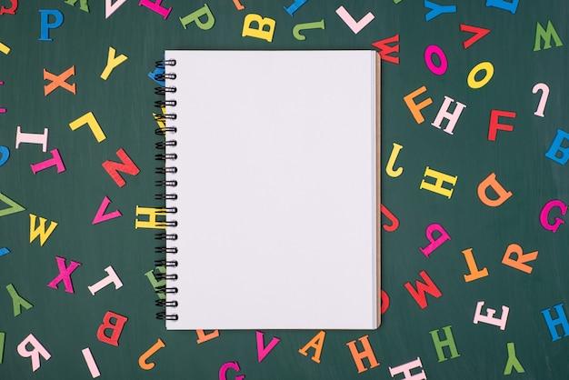 Estudando o conceito de escrita do colégio universitário. foto de visão aérea superior acima do caderno aberto vazio isolado em uma lousa com fundo de letras coloridas