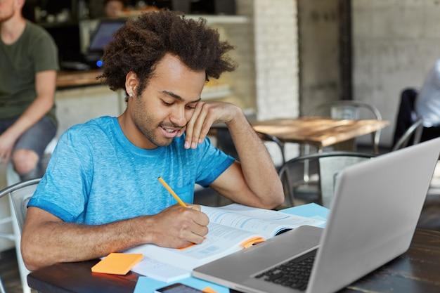 Estudante a trabalhador afro-americano de graduação vestida casualmente, fazendo anotações com lápis em um livro didático enquanto procura informações para o trabalho do curso, navegando na internet de alta velocidade em um laptop