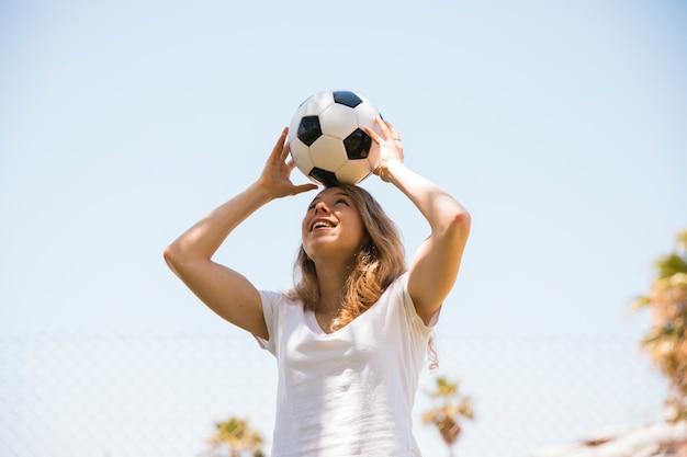 Estudante adolescente alegre segurando uma bola de futebol na cabeça