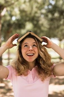 Estudante adolescente balanceamento de livro na cabeça