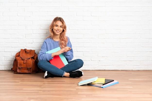 Estudante adolescente de cabelo rosa sentada no chão dentro de casa aplaudindo