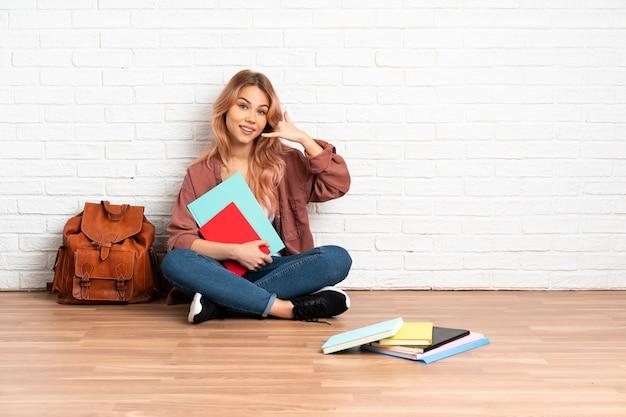 Estudante adolescente de cabelo rosa sentada no chão dentro de casa fazendo gestos de telefone e apontando para a frente