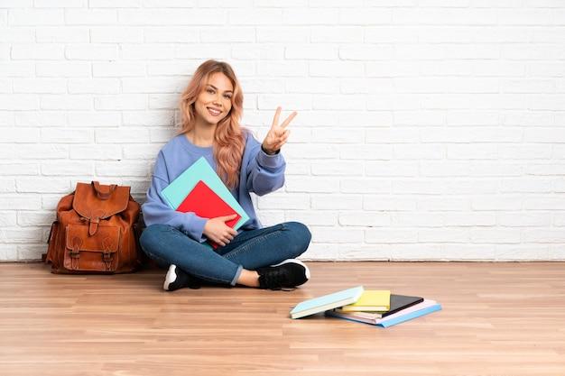 Estudante adolescente de cabelo rosa sentada no chão dentro de casa sorrindo e mostrando o sinal da vitória