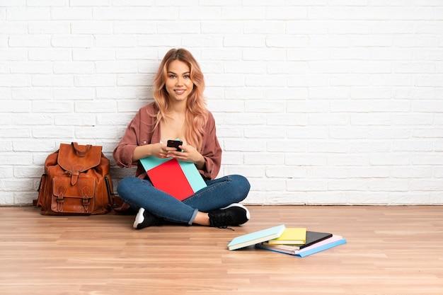 Estudante adolescente de cabelo rosa sentada no chão em uma casa enviando uma mensagem com o celular