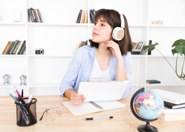 Estudante adolescente em fones de ouvido brancos, sentado à mesa com tablet