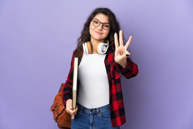 Estudante adolescente isolada em um fundo roxo feliz e contando três com os dedos