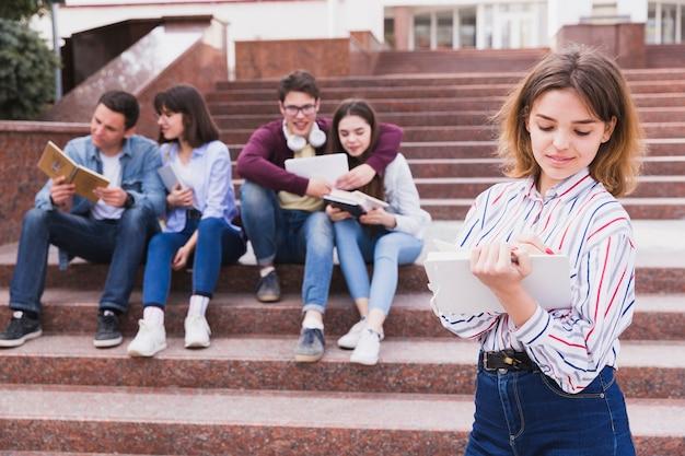 Estudante adolescente lendo livro segurando-o no centro de treinamento