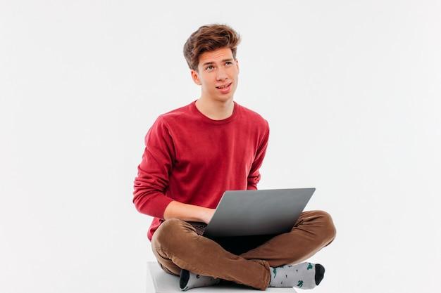 Estudante adolescente pensando e trabalhando no laptop em branco backgro