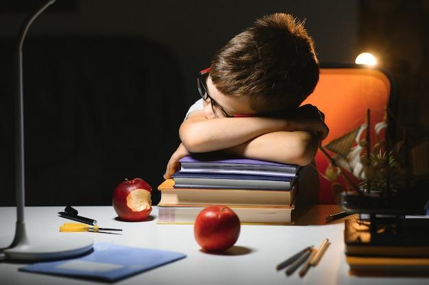 Estudante adolescente sentado à mesa fazendo lição de casa no quarto escuro