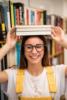 Estudante adolescente sorridente com livros na cabeça