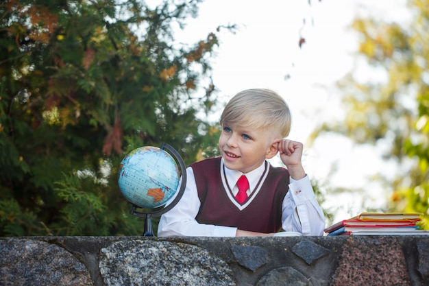 Estudante adorável com livros e globo no ar livre. educação para crianças. volta ao conceito de escola.