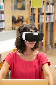 Estudante adulto feliz usando fone de ouvido vr durante o trabalho na biblioteca