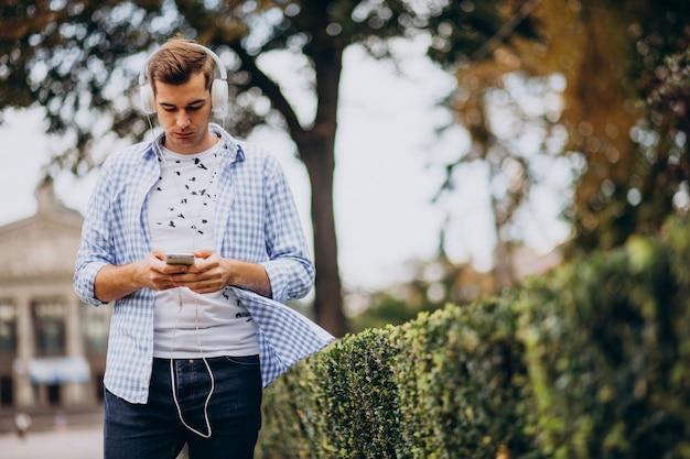 Estudante adulto jovem andando na rua com fones de ouvido
