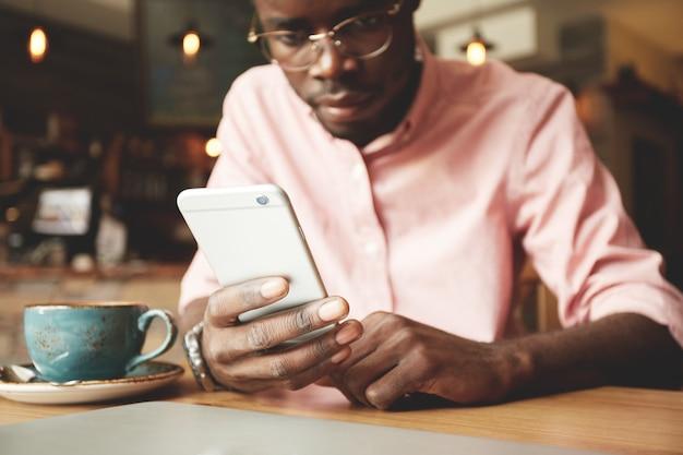 Estudante africano bonito de camiseta e óculos, usando telefone celular