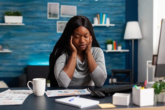 Estudante africano cansado e infeliz com dor de cabeça, sentado na mesa