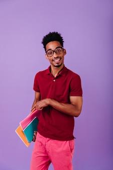 Estudante africano de olhos escuros posando com seus livros. cara esperto em óculos grandes da moda isolados.