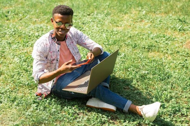 Estudante africano sentado na grama com laptop e telefone