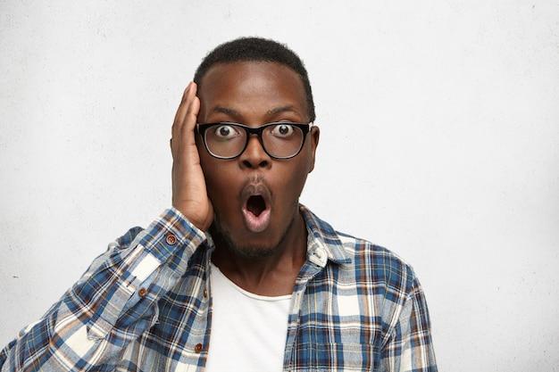 Estudante afro-americana esquecida em elegantes óculos, segurando a mão na cabeça, olhando com espantado olhar espantado, tendo esquecido completamente de um exame sério na faculdade.
