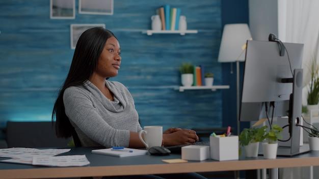 Estudante afro-americano acenando com professor durante reunião de videochamada virtual