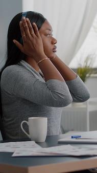 Estudante afro-americano, colocando fones de ouvido, ouvindo música divertida, digitando ideias de escola na internet usando a plataforma de e-learning no computador. mulher negra trabalhando longe de casa aproveitando o intervalo divertido