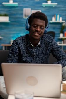 Estudante afro-americano com fone de ouvido e curso de negócios de áudio