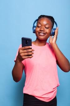 Estudante afro-americano com fones de ouvido segurando um smartphone