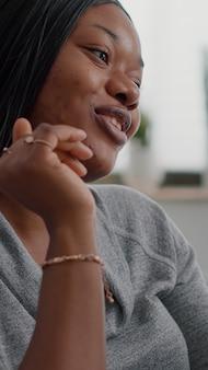 Estudante afro-americano conversando com um amigo, explicando aula de matemática online durante videochamada digital ...