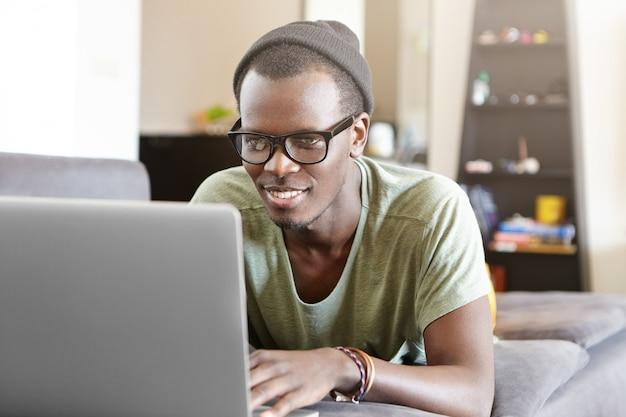 Estudante afro-americano de aparência moderna, desfrutando de conexão de alta velocidade à internet em casa, deitado no sofá com o notebook, assistindo séries online ou jogando videogame