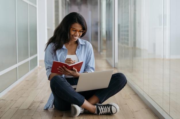 Estudante afro-americano, estudando, usando um laptop, fazendo anotações. freelancer feliz trabalhando em casa