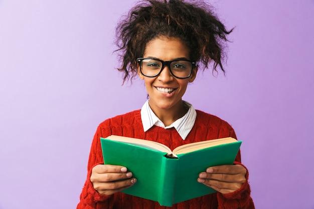 Estudante afro-americano feliz em uniforme segurando e lendo livro, isolado