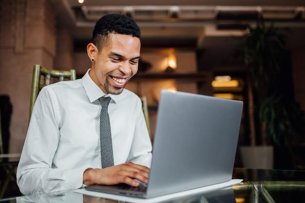 Estudante afro-americano feliz navegando na web no laptop