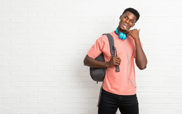 Estudante afro-americano novo do homem que faz o gesto do telefone e que fala com alguém. me ligue de volta