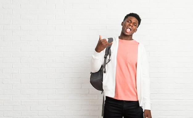 Estudante afro-americano novo do homem que mostra a língua na câmera que olha engraçada