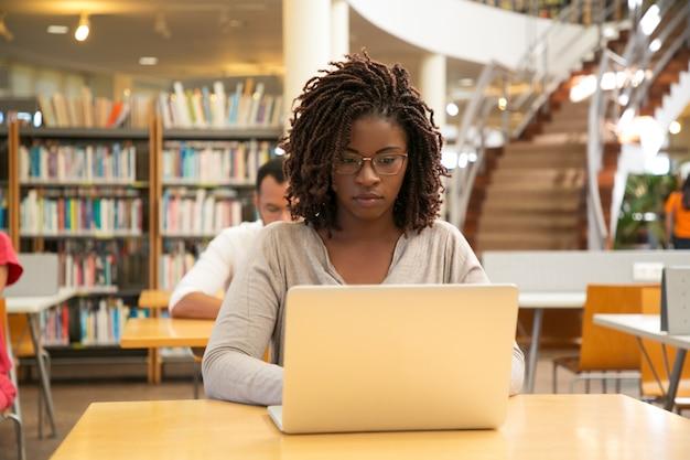 Estudante afro-americano sério trabalhando na pesquisa