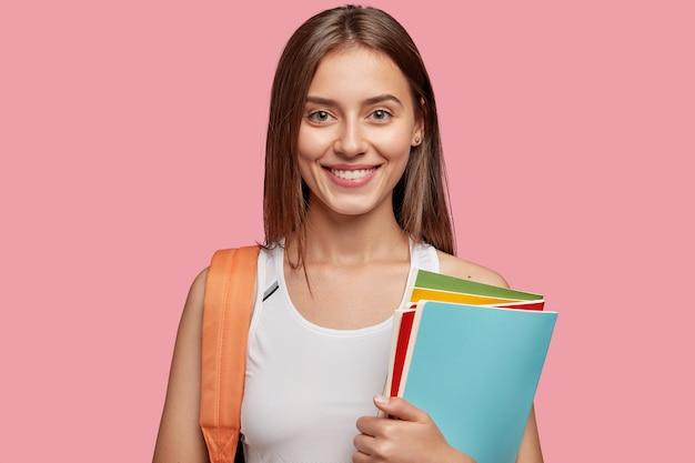 Estudante alegre posando contra a parede rosa