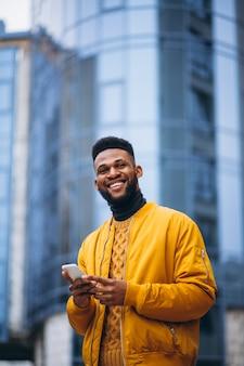 Estudante americano africano andando na rua e falar ao telefone