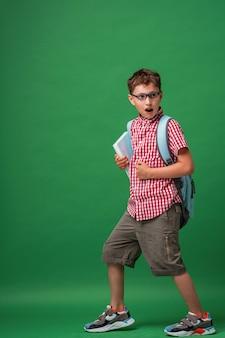 Estudante andando surpreso e chocado de óculos, segurando o livro e mochila