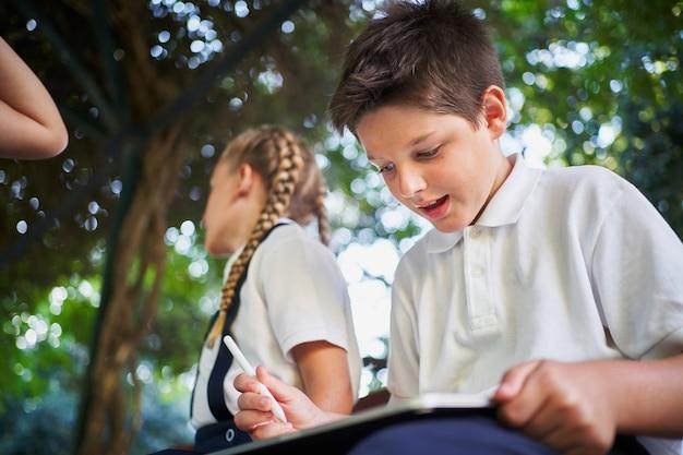 Estudante animado usando tablet com lápis digital em uma árvore