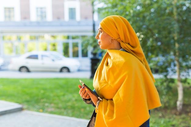 Estudante árabe. bela aluna muçulmana usando o tablet de exploração do hijab amarelo brilhante.