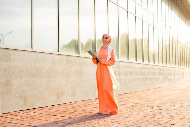 Estudante árabe segurando uma pasta. jovem bela mulher muçulmana andar na cidade.