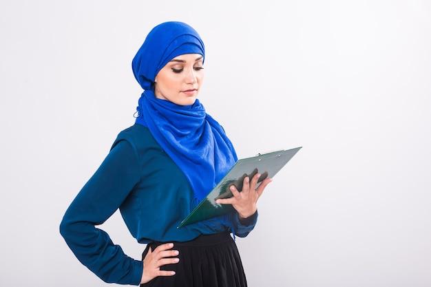 Estudante árabe segurando uma pasta no estúdio