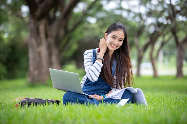 Estudante asiática bonita que guarda livros e sorrindo e aprendizagem e educação no parque no verão para relaxar o tempo