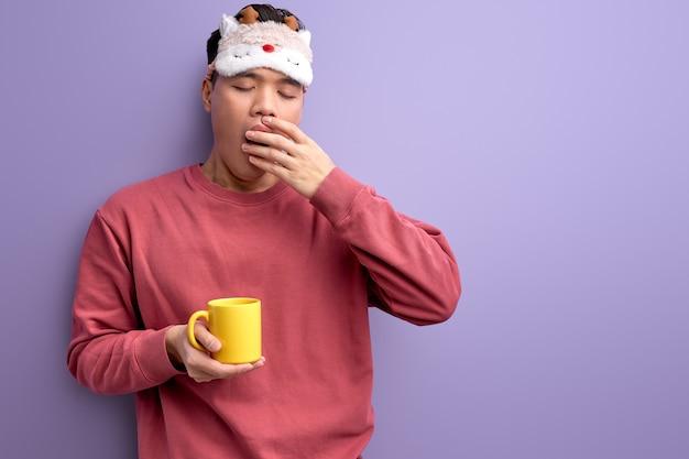Estudante asiática cansada com uma caneca nas mãos bocejando, quer dormir antes da escola ou universidade