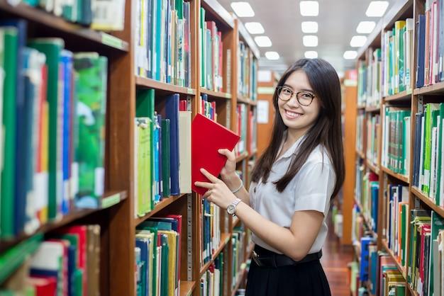 Estudante asiática colocando em ordem livros retornados após a leitura