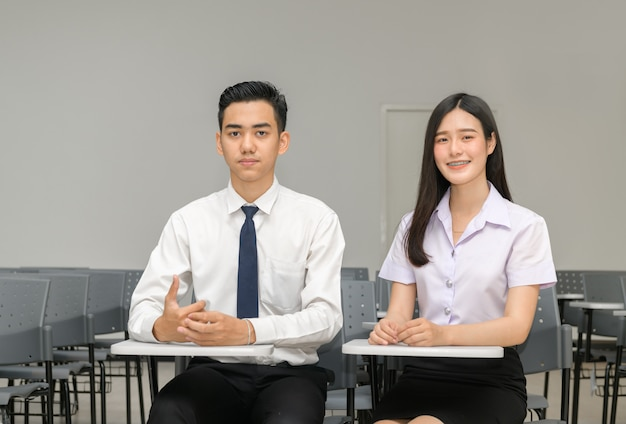 Estudante asiática com aparelho nos dentes e amigo em sala de aula