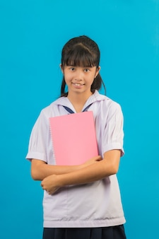 Estudante asiática com menina de cabelos longos, segurando um caderno em um azul.