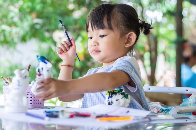 Estudante asiática desenhando e pintando as cores no papel da sala. estudo do conceito de casa, distância social, criança e educação.