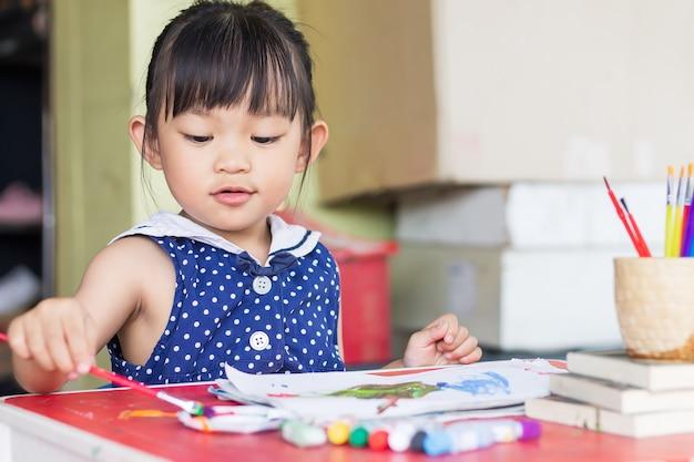 Estudante asiática desenhando e pintando as cores no papel da sala.