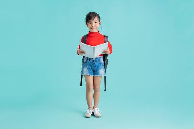 Estudante asiática, ela está abrindo o livro. no estúdio de fundo